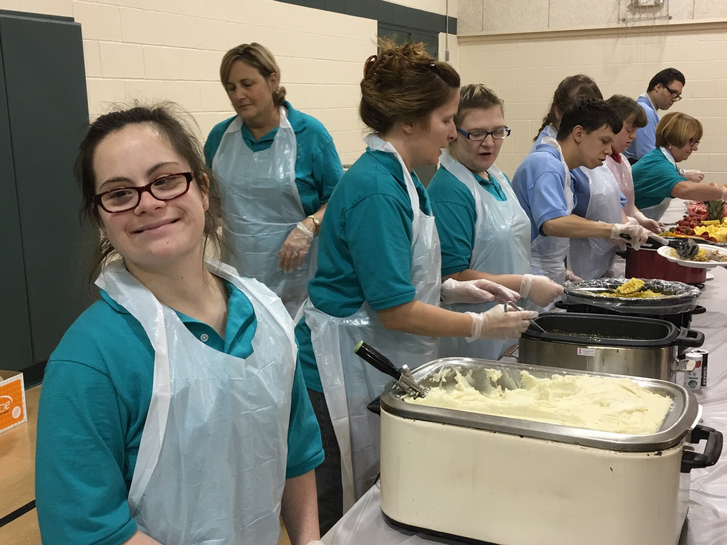 Students at the Waldron center are smiling in the matching uniforms as serve dinner to others.